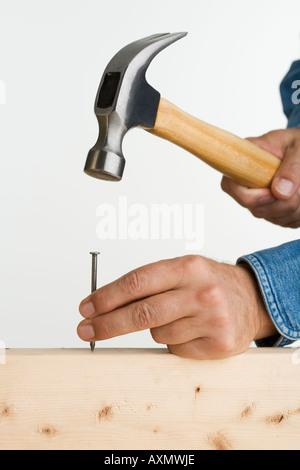 Close up of man using hammer and nail - Stock Photo