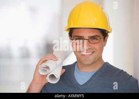 Man wearing hard hat and holding blueprints - Stock Photo
