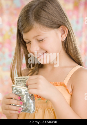 Young girl putting money in change purse - Stock Photo