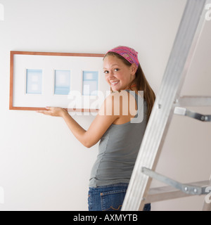 Young woman hanging picture on wall - Stock Photo