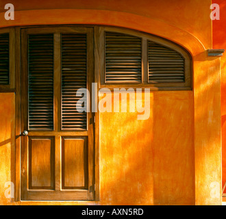 Nayarit Mexico Afternoon light rakes the woodend doorway and orange walls of a courtyard in the village of Bucerias - Stock Photo