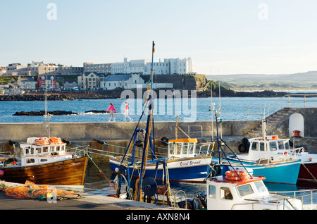 Seaside town of Portstewart, County Derry, Northern Ireland. Girls on harbour wall in front of the Dominican Convent. - Stock Photo