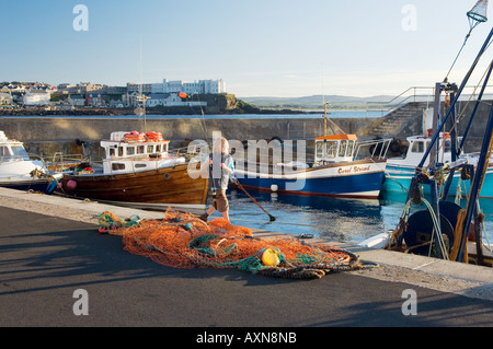 Seaside town of Portstewart, County Derry, Northern Ireland. Young girl with fishing rod and net in the harbour. - Stock Photo