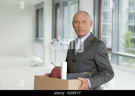 Elderly manager carrying a cardboard box, standing in an empty office - Stock Photo