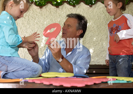 Gray-haired man is sitting between two kids while holding letters and numbers made of foam plastic in his hands - Stock Photo