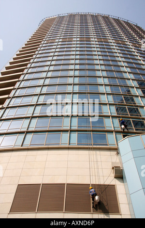 window cleaners at work on the vast expanse of glass on the facade of the new high rise  Hyatt on the Bund hotel,Shanghai,China - Stock Photo