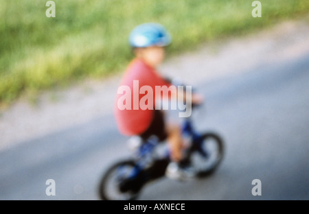 Defocussed young child in cycle helmet pedalling bicycle along lane - Stock Photo