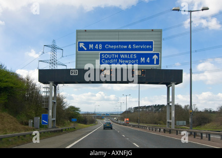 Horizontal view of cars driving underneath a motorway gantry sign with the matrix lights flashing to slow down. - Stock Photo