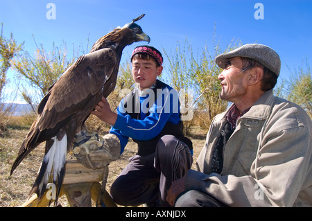 An eagle hunter trains his eagle and teaches his son the ancient Kazakh sport of eagle hunting Bayan Olgi Mongolia - Stock Photo