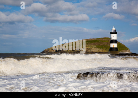 Rough sea in windy weather with Penmon lighthouse (Trwyn Du) and waves in foreground on rocky coast with Puffin - Stock Photo