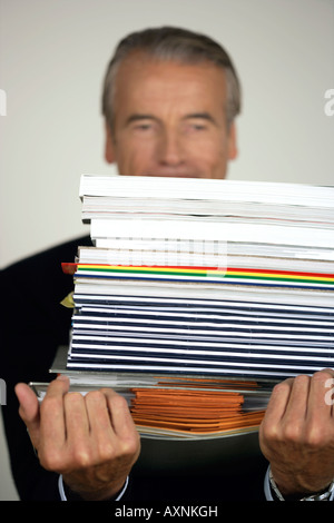 Senior businessman carrying a stack of documents - Stock Photo