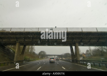 Horizontal wide angle view driving down the motorway in bad weather conditions - rain, sleet and snow. - Stock Photo
