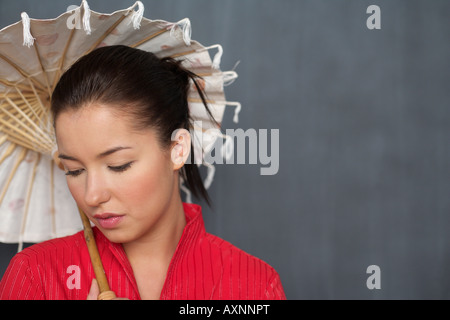 Asian woman is holding an umbrella in front of a blackboard, close-up - Stock Photo