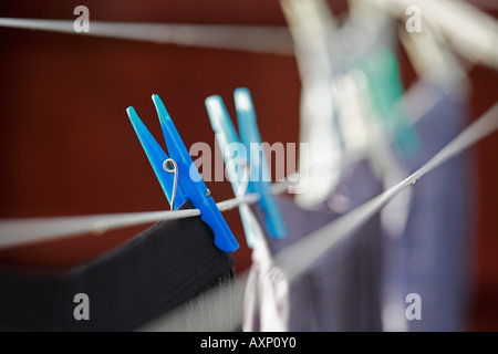 PEGS HOLDING WASHING ON THE LINE - Stock Photo