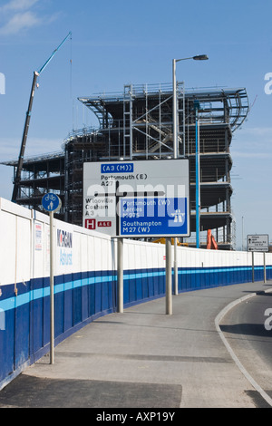 Road Junction Sign with office development behind in North Portsmouth and Cycle path Sign Hospital Accident and - Stock Photo
