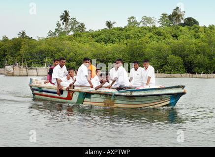 Schoolboys going to school by river boat, Galle, Sri Lanka - Stock Photo