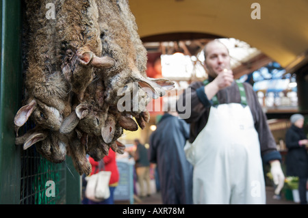 Hares strung up for sale in London's Borough market whilst a fish monger lights a cigarette in the background. - Stock Photo