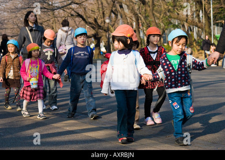 Young Japanese school children walking in a line holding hands in Ueno Park Tokyo Japan - Stock Photo