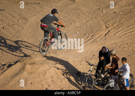 A group of youths performing improvised bike stunts - Stock Photo