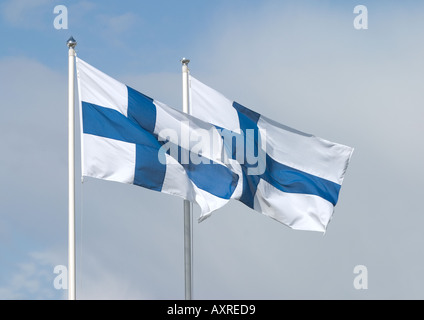 Two Finnish flags flying in the wind against blue and white sky - Stock Photo