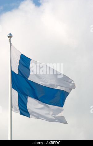 Flag of Finland flying in the wind against blue and white sky - Stock Photo