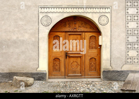 Entrance of an Engadin house decorated with Sgraffito ornaments in Scuol Schuls, Lower Engadin, Grisons, Switzerland - Stock Photo
