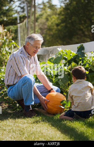 Grandpa and grandson looking at a pumpkin - Stock Photo