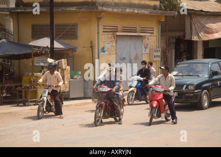 cars and motorcycles on a dirt road in Cambodia - Stock Photo