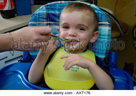 Mother feeding her toddler son yoghurt while he sits in highchair UK - Stock Photo