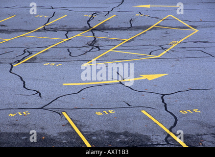 Arrows likes and cracks in an parking lot form an abstract pattern - Stock Photo
