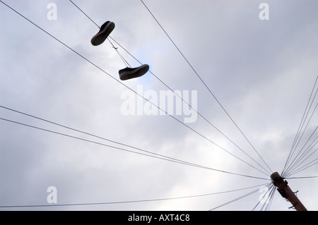 Trainers hanging from a telephone wire - Stock Photo
