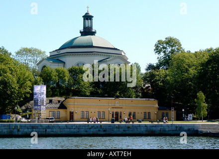 Waterfront museum with people sunning themselves on benches - Stock Photo