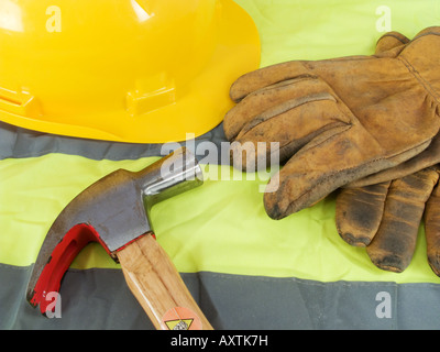 Yellow hardhat, old leather gloves, reflective vest and a hammer - Stock Photo