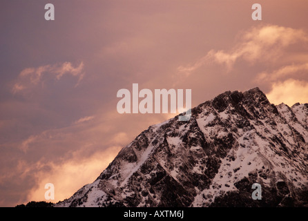 Last rays of setting sun with spectacular pink clouds closing in over snow covered ridge of Grands Montets, Chamonix - Stock Photo
