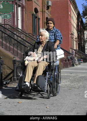 woman shoving another woman in wheel chair over sidewalk, USA, Manhattan, Harlem, New York - Stock Photo