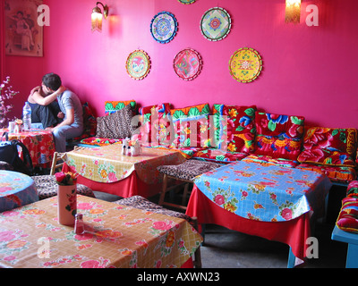 loving cuddling couple in colourful Antoine & Lili tea room Quai de Valmy 10th Arr. Paris France - Stock Photo