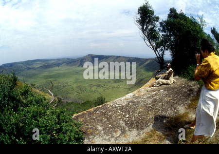 Lady tourist photographing spectacular view on Crater Drive Queen Elizabeth National Park Uganda - Stock Photo
