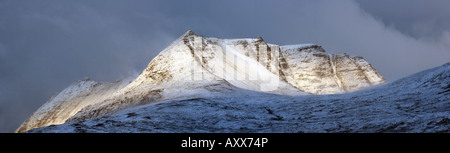 A brief burst of sunshine lights up the snow covered slopes of Ben Mor Coigach - Stock Photo