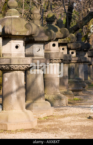 Row of giant stone lanterns lining the path to the Toshogu shrine in Ueno Park Tokyo Japan - Stock Photo