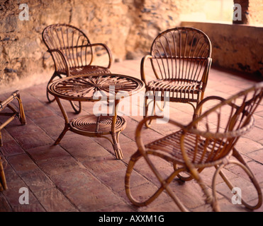 wicker chairs in stone courtyard spain - Stock Photo