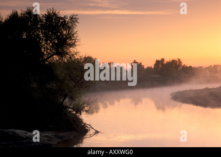 Mist at sunrise on bend in the San Joaquin river Great Grasslands State Park Merced County Central Valley California - Stock Photo