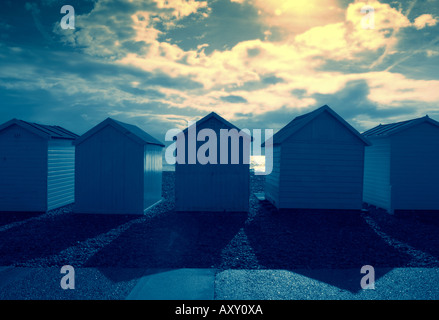 Blue beach huts under a yellow sky - Stock Photo