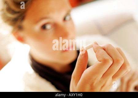 Woman looking doubtful at tablet - Stock Photo