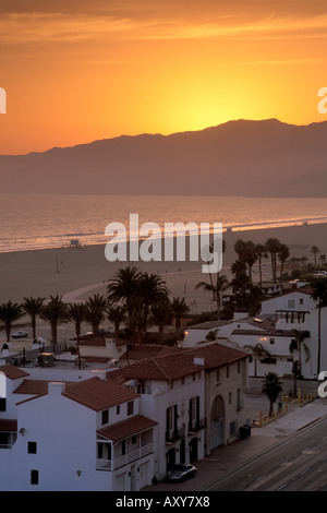 Sunset over coastal mountains and homes along sand beach at Santa Monica Los Angeles County California - Stock Photo