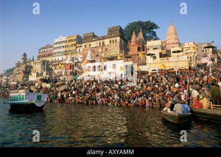 Hindu pilgrims bathing in the early morning in the holy river Ganges, Varanasi, Uttar Pradesh state, India - Stock Photo