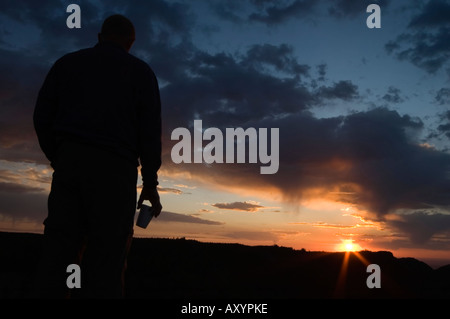 Man in silhouette with coffee cup watching the sunrise over the Big Horn mountains Wyoming USA after a long climb - Stock Photo