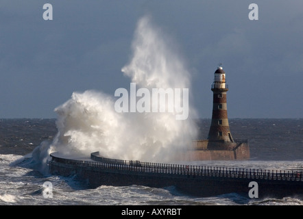 A huge ocean wave breaks over the Lighthouse on Roker Pier in Sunderland during a spring gale - Stock Photo