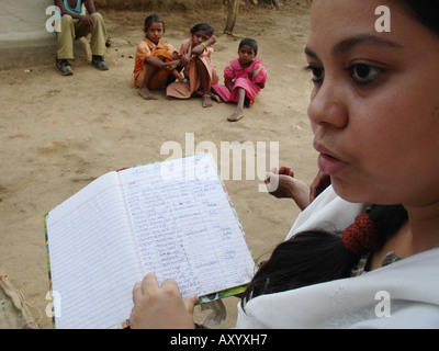 Teacher visiting inhabitants of a very remote and poor village in central India - kids waiting for the classes while - Stock Photo