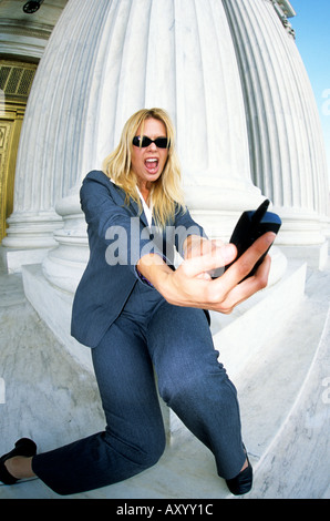 Businesswoman yelling into mobile phone Model Released - Stock Photo