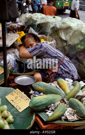 Old woman flower seller sleeping at stall, Bangkok - Stock Photo